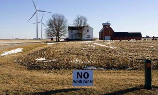 A sign near a farmhouse sited next to wind turbines reads 'NO WIND FARM'. The Donors Trust and Donors Capital Fund served as the bankers of the conservative movement over the past decade, have funded a campaign against windfarms. Photo: Alex Garcia / Getty Images