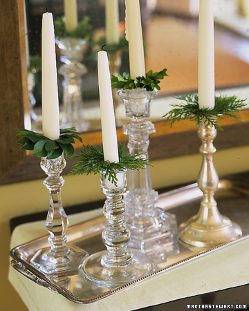 This is the simplest way to add greenery to any room. Tuck greenery into your candlesticks and use it as bobeches, those little glass collars meant to catch dripping candle wax.