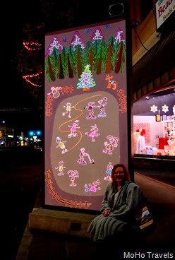 Deb with the Lighted musical Christmas panels in towntown Grants Pass