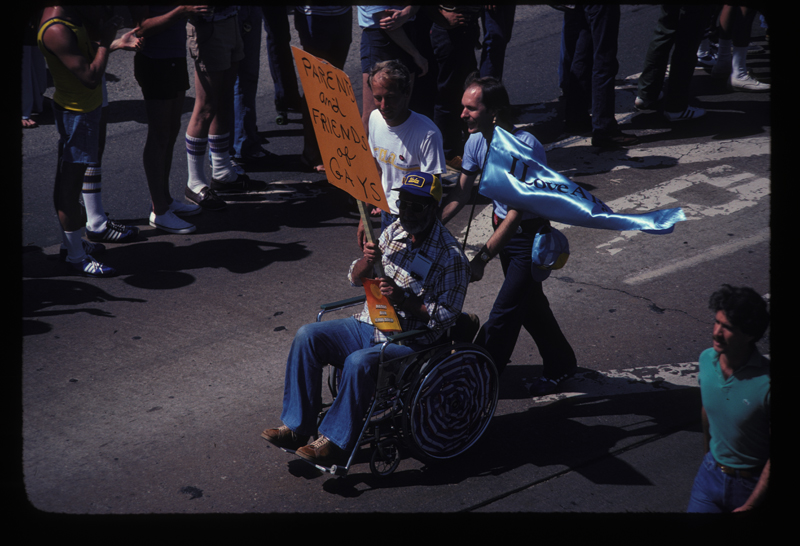 Man in wheelchair supporting the Parents and Friends of Gays at the Los Angeles Christopher Street West pride parade. 1979.