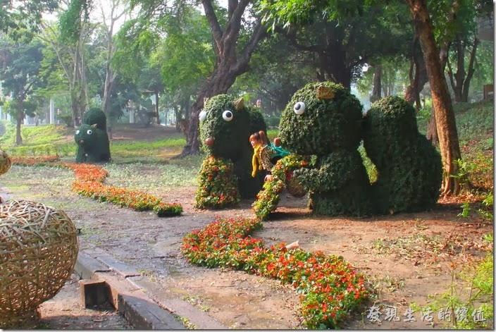 台南-2014中山公園百花祭。裝置都還沒真正完成,已經有美眉等不及與松鼠合影了,不過這個動作真的不建議,這樣會踐踏草皮並有機會破壞裝置藝術啊。