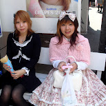 Gothic Lolita and Victorian Lolita girls sitting on a bench eating a crepe in Harajuku, Tokyo, Japan