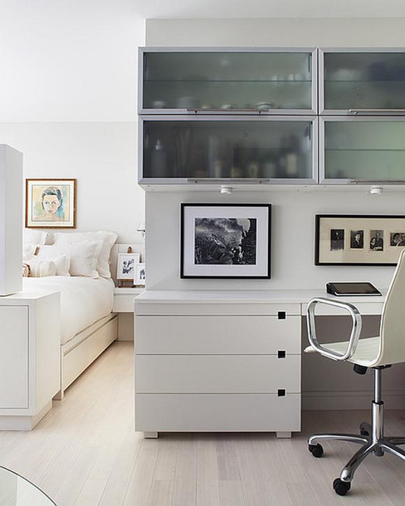 Habitación blanca y luminosa de invitados con pequeña oficina
