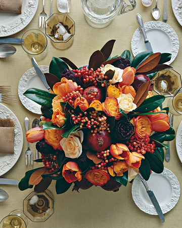 Pomegranates, red viburnum berries, tulips, roses, ranunculus, and a bronzy-green magnolia-leaf wreath are all used to create the perfect Thanksgiving centerpiece.