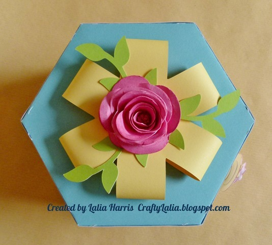 3D rolled rose and 3d paper ribbon top the Artiste exploding hexagon box.  Created by Lalia Harris