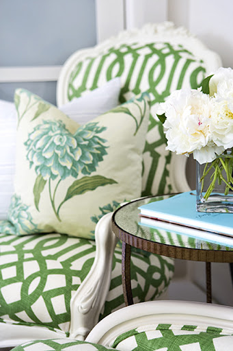This chair is covered with an emerald latticework pattern that invites in all kinds of cooler florals, such as the pillow displays. Using a prop book to bring a burst of color is an easy decorating trick. (www.krishelmick.com)