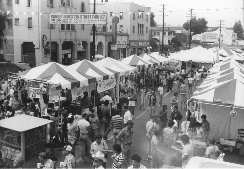 Attendees survey the kiosks at the Sunset Junction Street Fair. August 21-22, 1982.