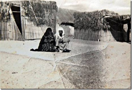 Fujairah, Al Faseel neighbourhood. UAE. 1970 (date unknown) Photo shows Abdullah bin Khaten (right) and his wife Mozah Mohammed holding her grandaughter Mariam Al Kaabi. They are sitting outside their home made of areesh (date palm) The photograph was taken by a British man, possibly a tourist who was touring the Gulf at the time.  Courtesy of Bin Kateem family.   Ramadan Feature for Weekender