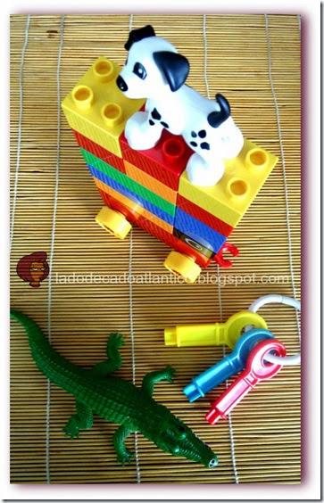 Imagem de brinquedos: um cão sobre uma torre de Legos, um crocodilo e um molho de chaves