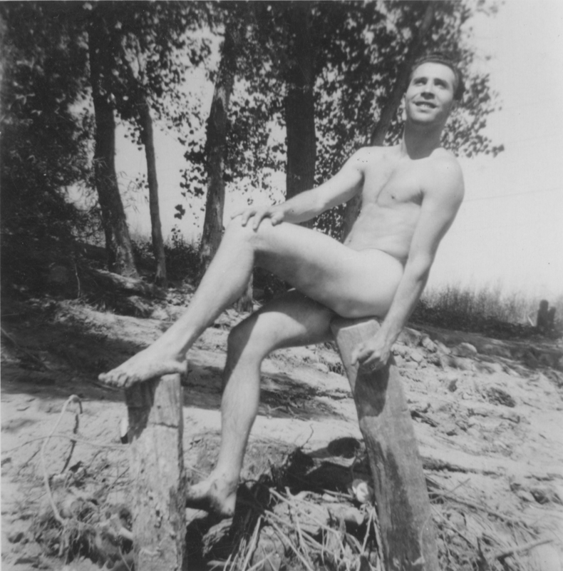 Pat Rocco sitting naked on a stump. Undated