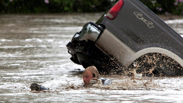 A Canadian man and his cat swam for their lives as the flood waters submerged his truck in High River, Alberta. Kevan Yaets holds his cat Momo after his truck was caught in rising flood waters in Alberta, Canada, on Thursday. Officials say up to 100,000 Canadians could be displaced by the severe flooding. Photo: Jordan Verlage / AP
