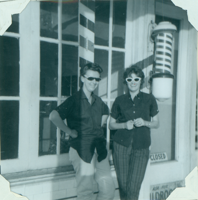 Adrian Smart and Carolyn Weathers stand outside a barbershop. Spring 1963.