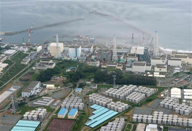 An aerial view shows Tokyo Electric Power Co. (TEPCO)'s tsunami-crippled Fukushima Daiichi nuclear power plant and its contaminated water storage tanks (bottom) in Fukushima, in this photo taken by Kyodo on 20 August 2013. Photo: REUTERS / Kyodo