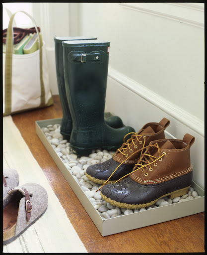 A  tray in an entryway keeps boots and shoes neat and contained.  In the spring, add some river rocks to help the water drain off and evaporate.