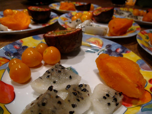 Uchuvas are the small round fruit on the left, the clearish fruit with black seeds is Pitaya, Zapote is the orange fruit on the right, and Coruba is the purplish fruit.