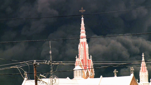 Smoke from a massive fire sparked by the derailment of a train carrying crude oil rises behind a church spire in the eastern Quebec town of Lac-Megantic Saturday, 6 July 2013. Photo: CTV News