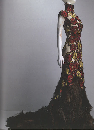 McQueen pairs the daisy print with a feathered train, lending the gown a more serious and elegant style.