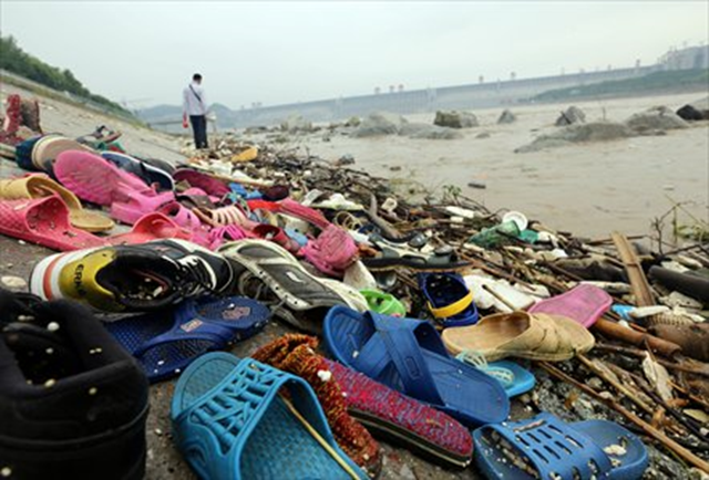 Shoes and other debris are swept ashore in Yichang, Central China's Hubei Province, on Sunday, 21 July 2013. Flood water was discharged from the Three Gorges Dam, a gigantic hydropower project on the Yangtze River, on Sunday. The Yangtze River braced for its largest flood peak so far this year due to continuous rainfall upstream. Photo: CFP