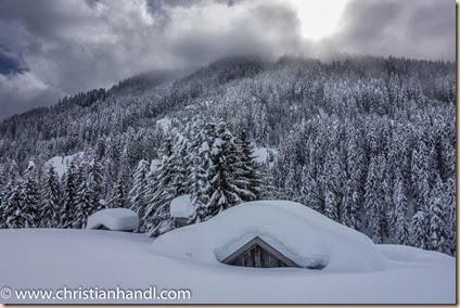 Holzhütte von viel Schnee bedeckt