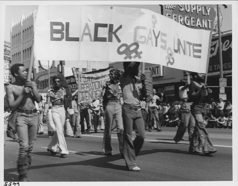 "Men hold a ""Black Gays Unite"" banner at the Los Angeles Chirstopher Street West pride parade. 1975."