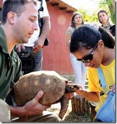 Homem segura uma tartaruga; moça cega passa a mão no animal