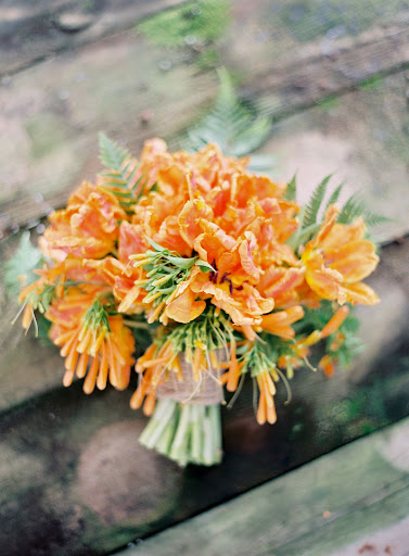 The bouquet features orange 'Monarch Parrot' tulips and foraged trumpet vine -- it grows rampant during California's winters.