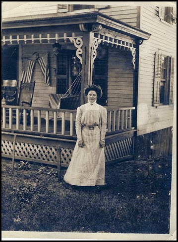 Lindsay_Marie in front of house with porch & flags circa 1912