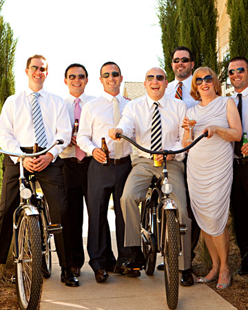 These groomsmen sporting different brightly patterned ties  mounted bicycles for a portrait with the groom and his mother.