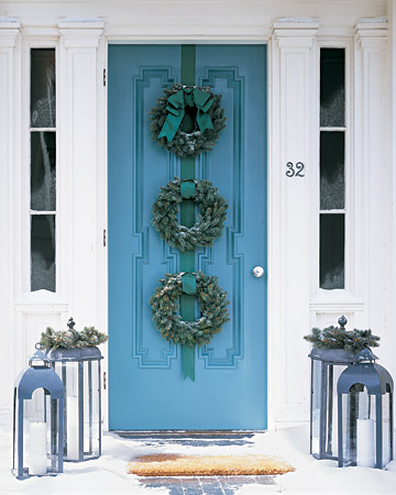 Instead of just one wreath adorning your door, tie three wreaths together with thick ribbon.