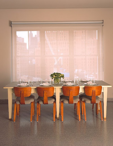 The dining table seats eight on Thonet chairs from the fifties. The table itself, a massive library table refinished with auto-body paint and a new linoleum top, seems to hover over the view south, toward the tip of Manhattan.