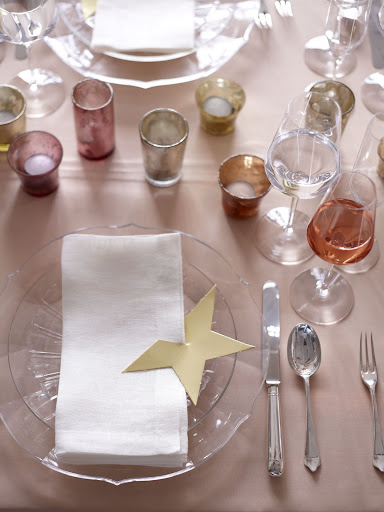 Set the table with simple pieces -- a peachy-pink tablecloth, glass dinnerware, off-white napkins -- to temper the bolder elements, like the mercury-glass candleholders and this gold-star napkin holder. (Martha Stewart Weddings)
