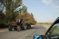 Old Russian tractor with a cart full of hay on the road from Bishkek to Osh