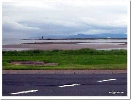 Isle of Arran hidden in cloud with a ferry crossing to Ardrossan. We assume the pinnacle is a light house.