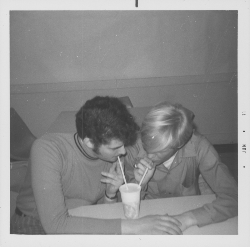 Gay couple, possibly students from the University of Rochester, New York, sip from the same drink while holding hands. June 1971.