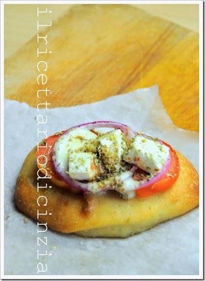 pizzette o mini schiacciate con feta origano pomodoro e rondelle di cipolla di tropea