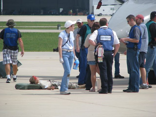 Actors posing as injured passengers in the drill wait for emergency responders to attend to them.