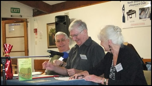 Holding the AGM. The microphone kept drooping more and more which seemed to cause huge amusement. Left to Right: Jim Nicholson (outgoing Treasurer); Gordon Sutherland (President); and, Delyse Whorwood (Secretary). Photo courtesy of Dennis Lyons.