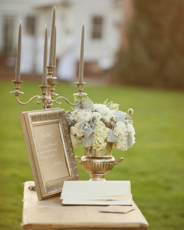 This guest book table, set out in the wide-open field where the ceremony took place, was decorated with an antique silver candelabra and a flower-filled urn.