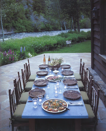 A cozy summer meal is set on the terrace on the edge of the Big Wood River shaded by the Bald Mountains -- complete with local farmers' market cuisine and American rustic furniture.