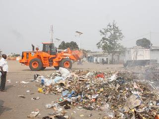 Un homme regardant un tas d'immondices déposés sur un terrain municipale de football à Kinshasa
