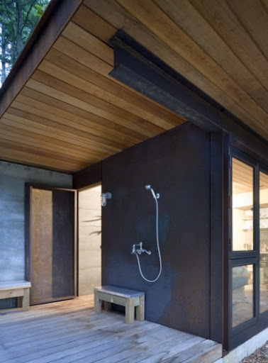 I love how minimalist this outdoor shower design is. It matches the modern architecture of the house perfectly.