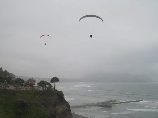 Paragliders over the rocky cliffs of Miraflores, Lima
