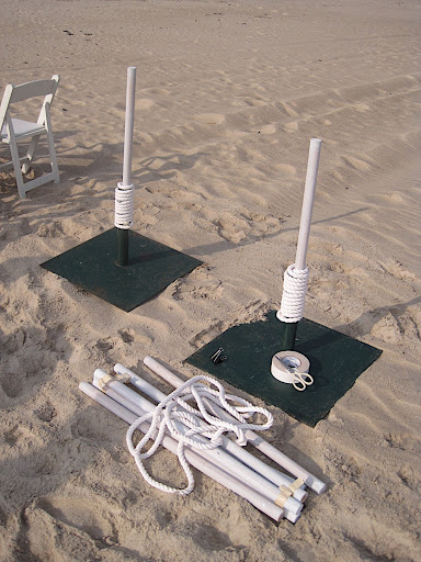 We buried umbrella stands in the sand for the ceremony structure and used the same tactic for poles along the aisle.