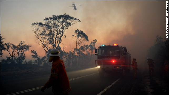 New South Wales Rural Fire Service crew members fight a fire near Mount Wilson in the Blue Mountains of Australia on 24 October 2013. Wildfires threatened the western suburbs of Sydney on Wednesday as high winds and temperatures created at least a dozen new fires that were blazing across a 1,000-mile stretch of New South Wales. Photo: Dan Himbrechts / AAP / LANDOV