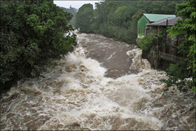 Floodwaters rush down Hilo's Wailuku River in 2000. Hawaii is seeing more frequent heavy storms, and climate change may be the reason, according to University of Hawaii researchers Ying Chen and Pao-Shin Chu. Photo: Hawaii Department of Public Works