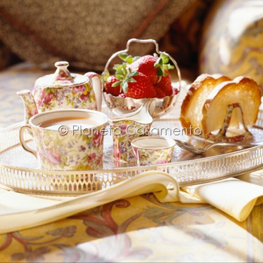 Teapot, strawberry and loaf of bread on table