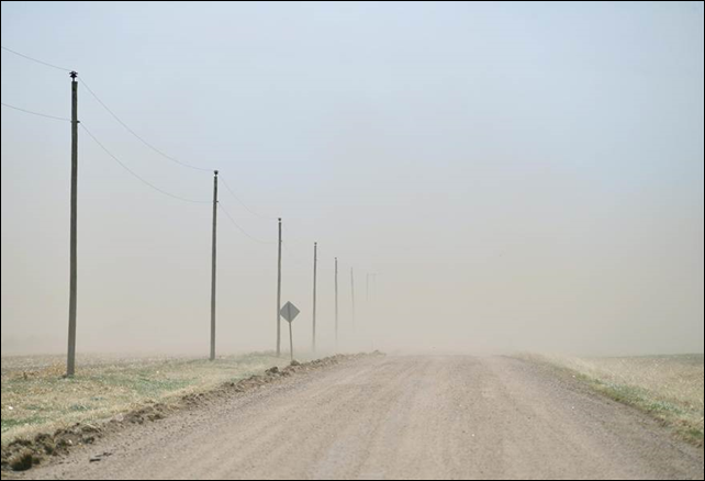 The relentless Kansas wind strips a dry, bare field and sends the topsoil to obscure a county road. Photo: Gil Aegerter / NBC News