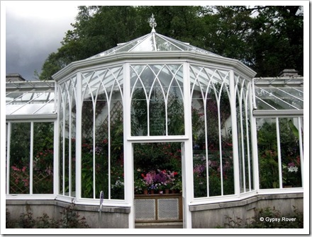 """Balmoral Castle gardens where exotic flowers are grown in the glass house. The engraving above the door reads """"One is nearer God's heart in a garden than anywhere else on earth""""."""