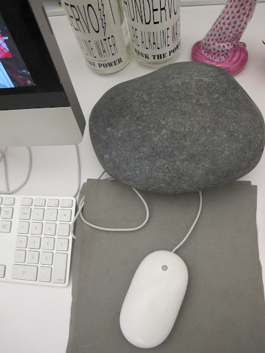 The layered paper beneath my computer mouse is complemented by the decorative rock behind it. Technology can be a great starting point for creative decor.