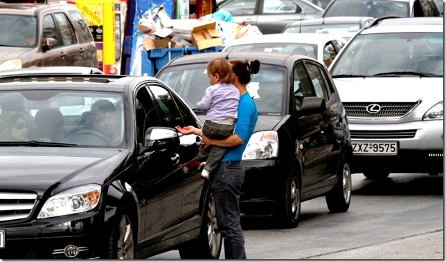 A woman carrying small child begs at a traffic light in the upscale suburb of Glyfada, south of Athens on Monday, Nov. 22, 2010. Greek charity groups have warned of a surge in homelessness and poverty in the Greek capital, caused by the recession and drastic austerity measures taken by the eurozone member to avoid bankruptcy and receive international bailout loans. (AP Photo/Dimitri Messinis)